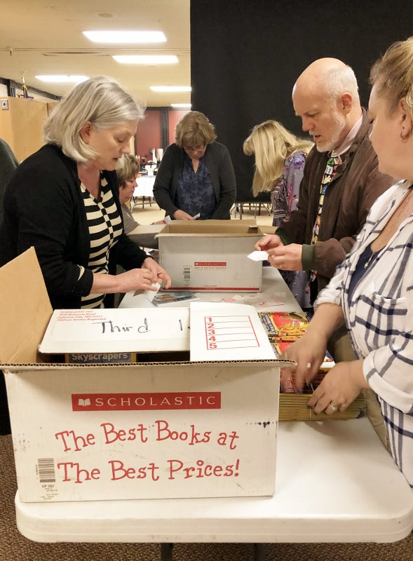 Canby Rotary members placing book plates in Scholastic Books for Elementary Children